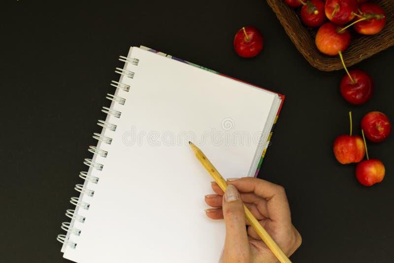 与笔记本的工作区和在黑粉笔板背景的红色苹果 女性手在日志拿着一支铅笔并且写计划 免版税图库摄影