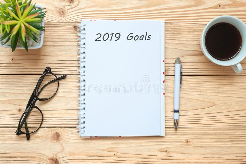 与笔记本的2019个目标、无奶咖啡杯子、笔和玻璃在桌上,顶视图和拷贝空间 新年新的开始,决议,Sol 库存图片