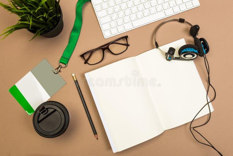 与笔记本键盘笔记本徽章耳机咖啡和玻璃的办公桌桌假装模板 顶视图 库存照片