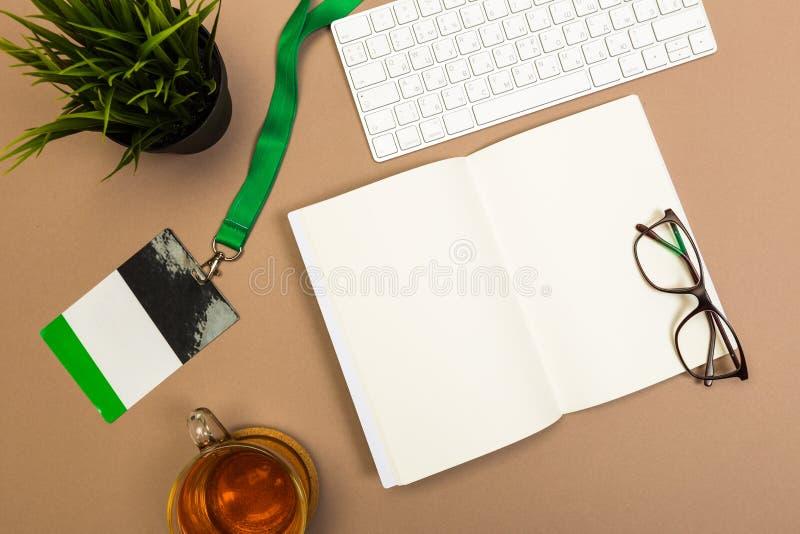 与笔记本键盘笔记本徽章茶杯和玻璃的办公桌桌假装模板 顶视图 免版税库存照片
