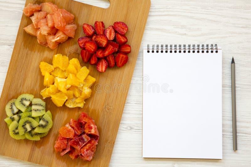 与笔记本,顶视图的各种各样的切好的果子 平的位置 库存照片