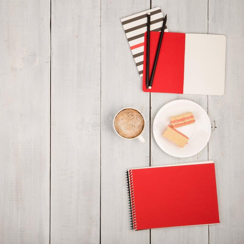 与笔记薄、咖啡和奶蛋烘饼的办公室桌在白色w 库存照片