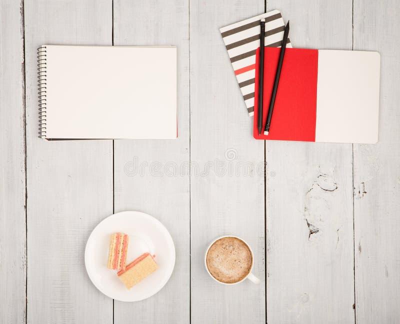 与笔记薄、咖啡和奶蛋烘饼的办公室桌在白色w 免版税图库摄影