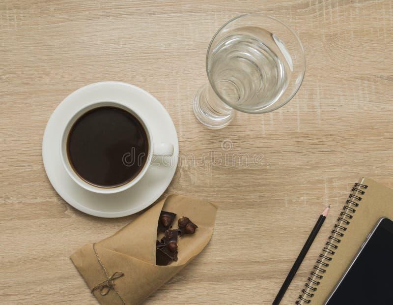 与笔记薄、巧妙的电话、咖啡杯、杯水和黑暗的巧克力的办公室桌 工作地点顶视图  图库摄影