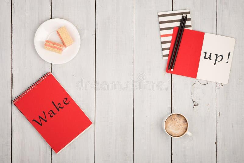 与笔记薄的办公室桌和文本& x22; 醒! & x22; 咖啡和奶蛋烘饼 免版税库存图片