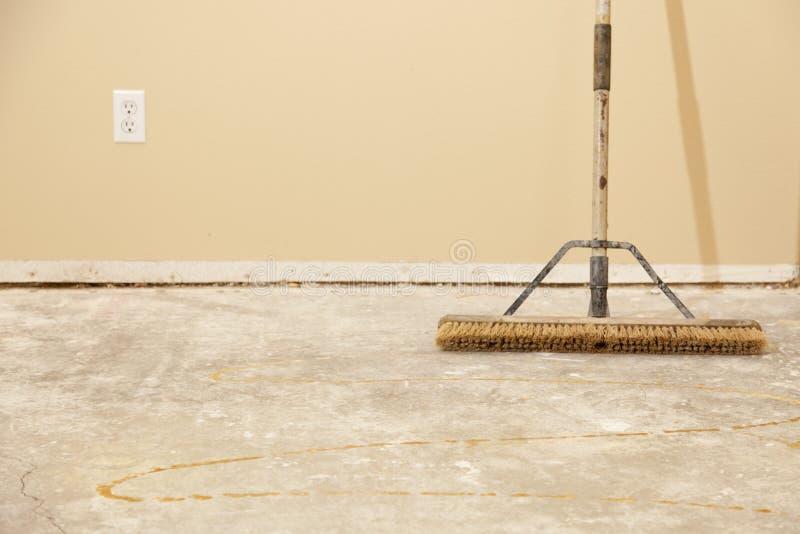 与笤帚的水泥之家楼层准备好难倒安装 免版税图库摄影
