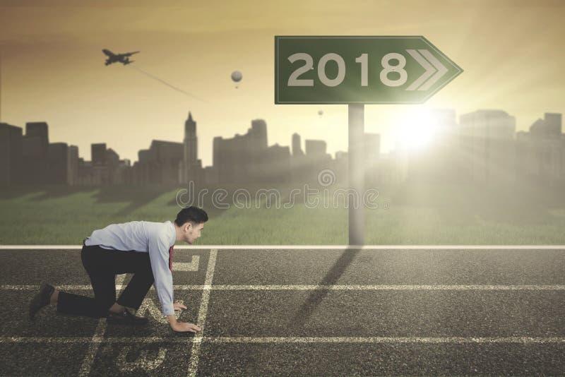 与第的年轻商人2018年在路标 库存图片