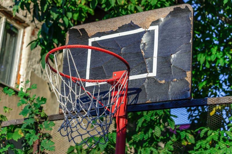 与笼子、树和房子的老和损坏的篮球篮的 免版税库存照片