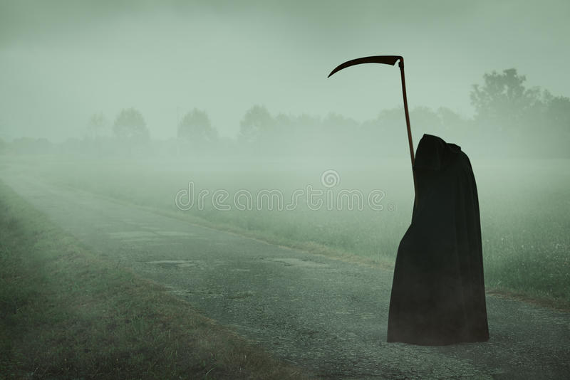 与等待在一条有薄雾的路的大镰刀的死亡 免版税库存照片