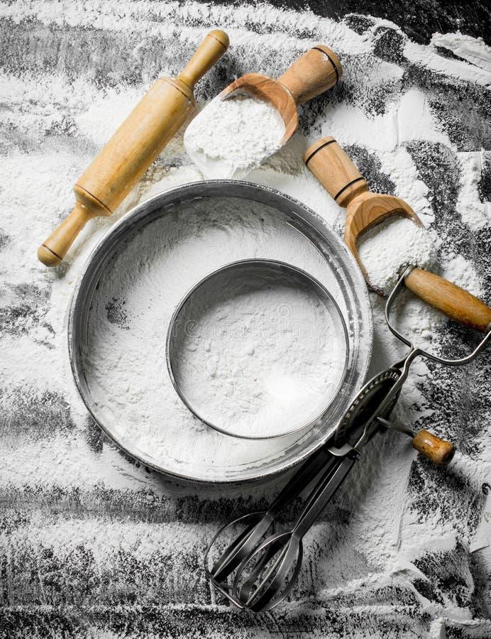 与筛子、瓢、滚针和搅拌器的面粉 免版税图库摄影
