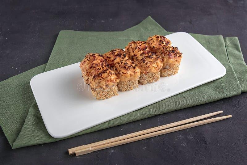 与筷子的被烘烤的寿司卷在一块白色板材 绿色餐巾和灰色背景 日本料理特写镜头视图在餐馆 免版税库存图片