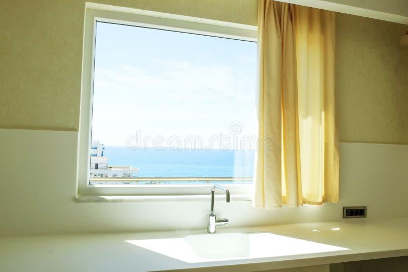 与简单的minimalistic现代室内设计的美丽的太阳边公寓,开放学制厨房客厅在阳光下 免版税库存图片