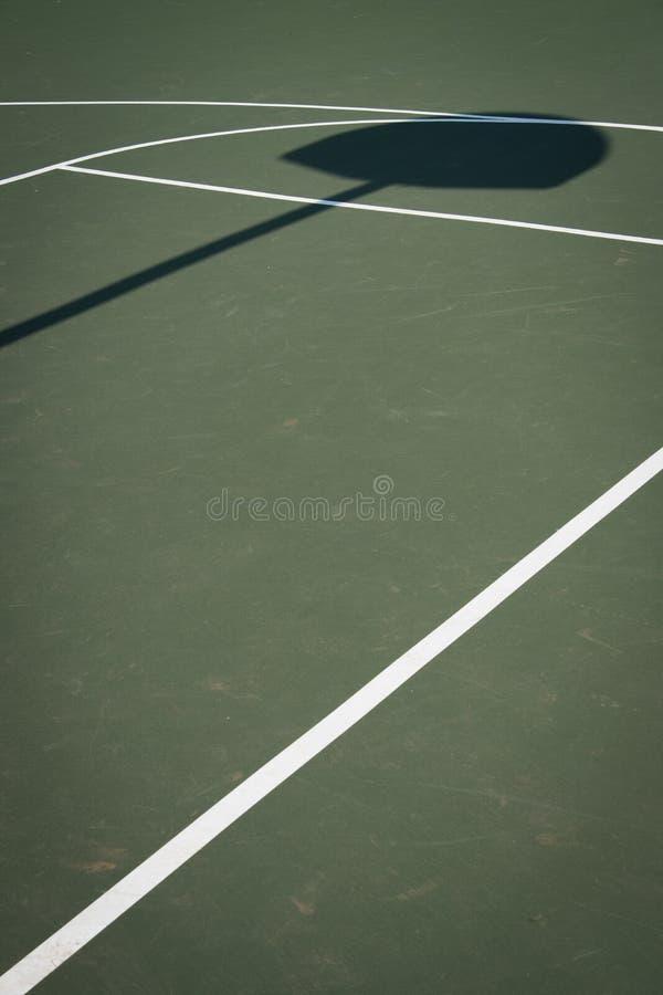 与箍阴影的绿色篮球场 免版税库存照片