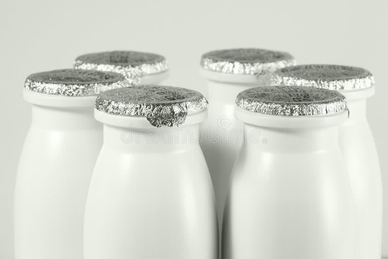 与箔盖帽的瓶用酸奶 免版税库存照片