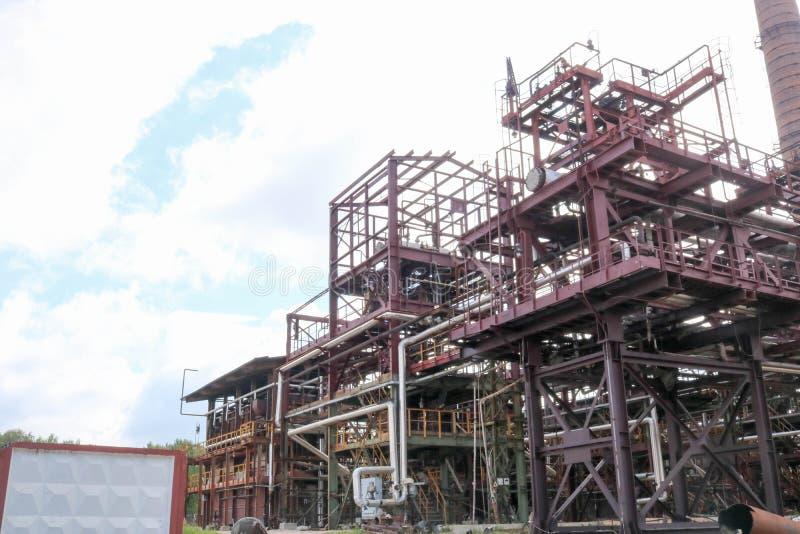 与管子的一个大铁金属管道系统的支架和电导线和设备在石油化学的精炼厂工业精炼厂 库存图片