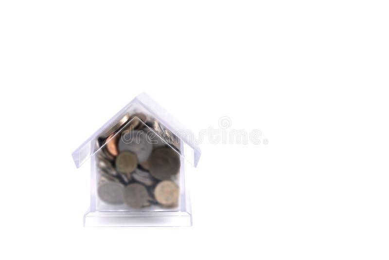 与管子的家猪 白色背景的透明塑料房子 在从不同的存钱罐金属硬币 库存照片
