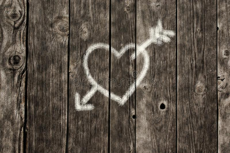 与箭头的心脏在老木板条 免版税库存图片
