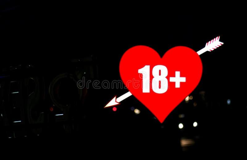 与箭头的红色霓虹心脏在夜背景 图库摄影