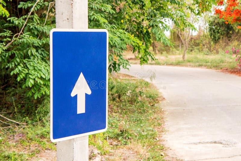 与箭头、迷离树和路背景的蓝色标志 免版税图库摄影