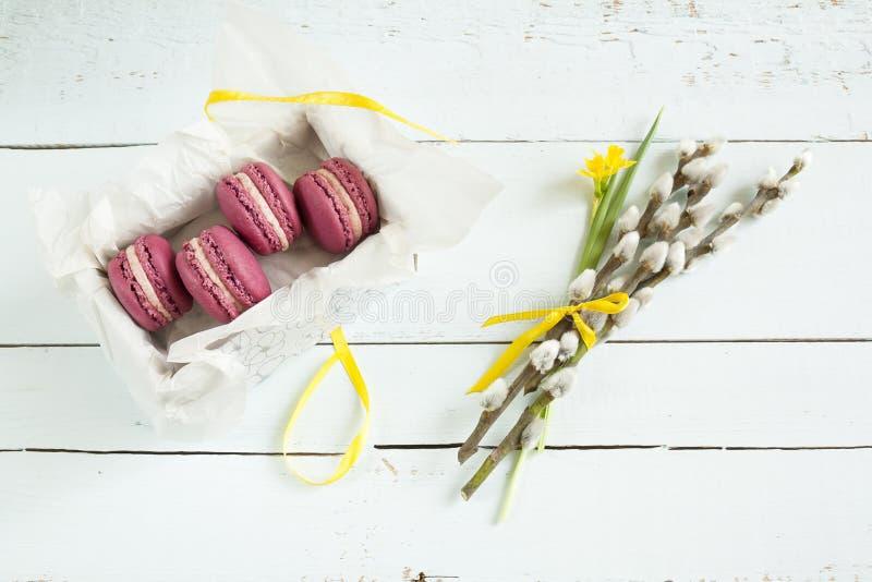 与箱子、黄水仙(水仙)和褪色柳的甜绯红色法国蛋白杏仁饼干在光洗染了木背景 免版税库存照片