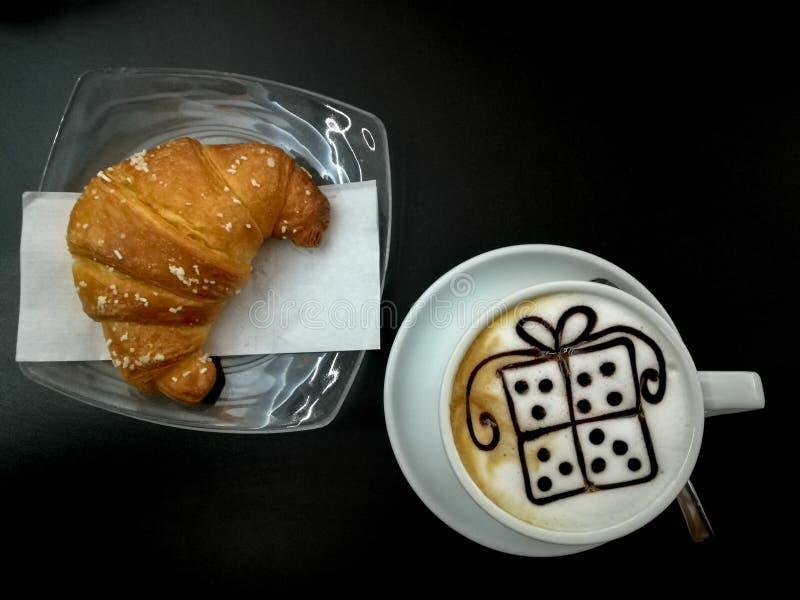 与箱子礼物形状装饰的热奶咖啡 免版税库存照片
