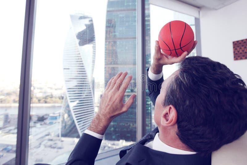与篮球的生意人 免版税库存照片