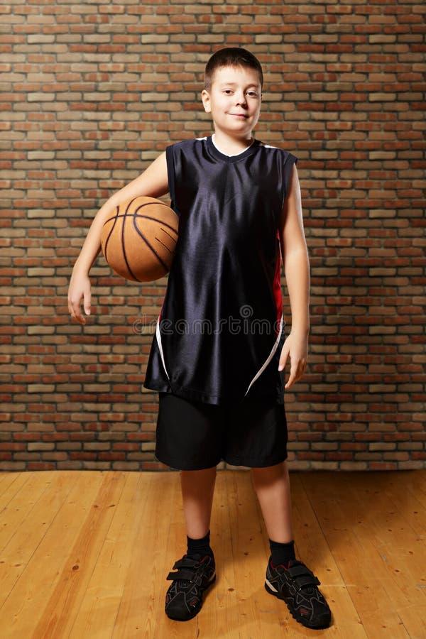 与篮球的满足的孩子 免版税库存照片