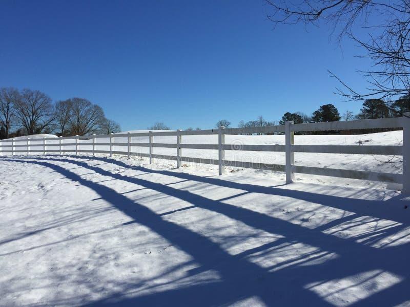 与篱芭的积雪的小山 免版税图库摄影