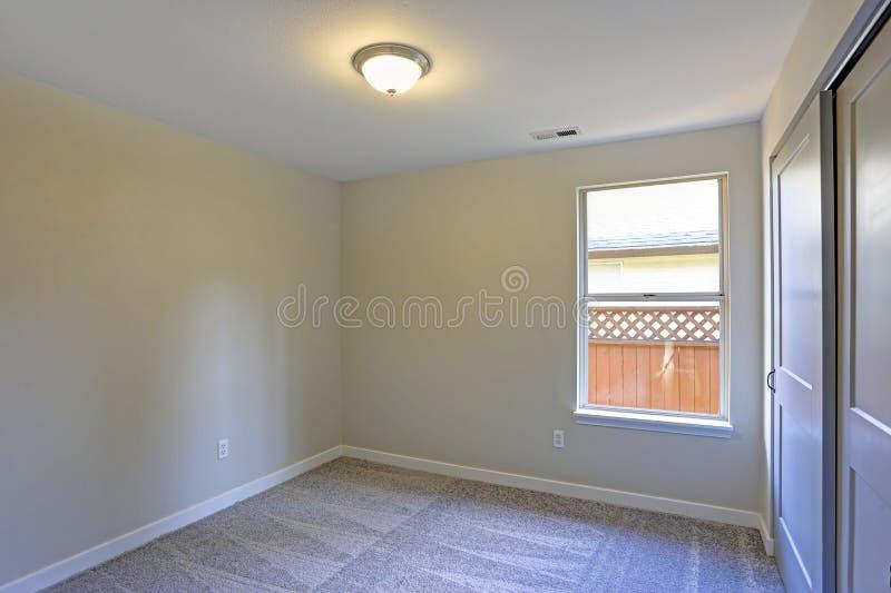 与米黄墙壁和墙到墙的地毯的空的室内部 库存图片