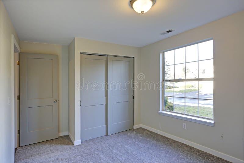 与米黄墙壁和墙到墙的地毯的空的室内部 免版税图库摄影