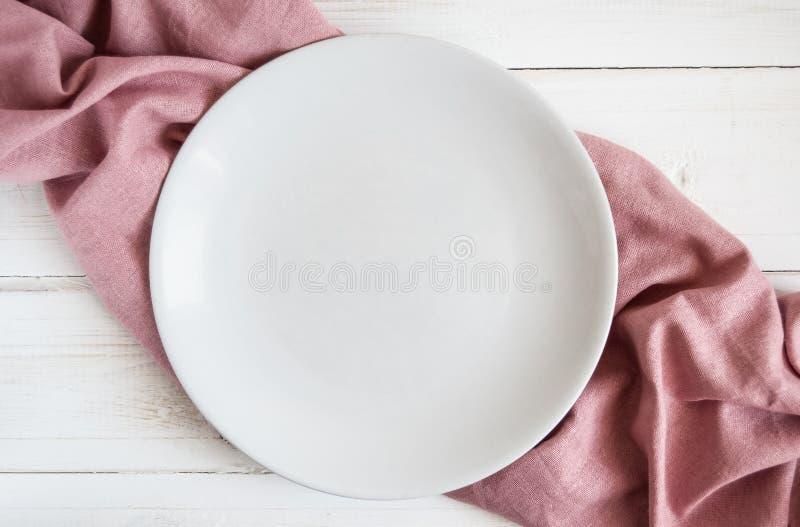 与粉色薄荷的餐巾的木白色桌与一块空的板材的 免版税图库摄影