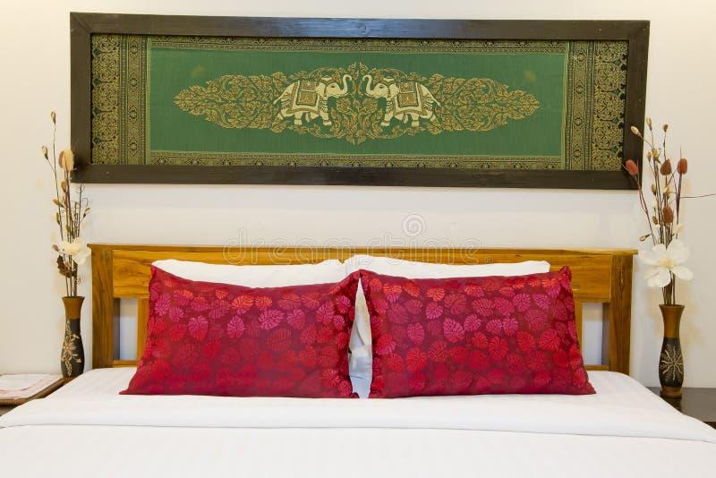 与精密丝屏罩的现代亚洲式床有在bedro的框架的 库存照片