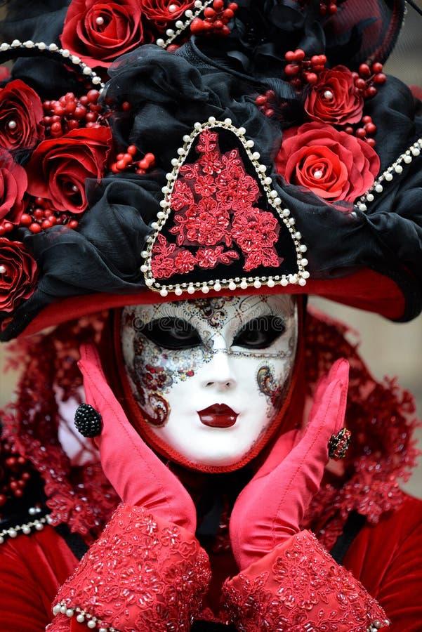 与精心制作的帽子的红色狂欢节面具在威尼斯,意大利 免版税图库摄影