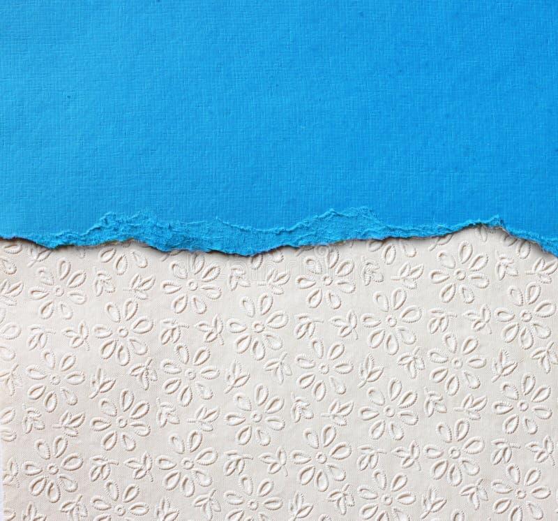 与精美条纹样式和蓝色葡萄酒被撕毁的纸的老帆布纹理背景 免版税库存照片