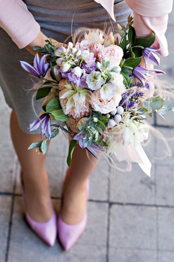 与精美花的美丽的花束 桃红色白色紫色花束 新娘花束在女性手上 免版税库存照片