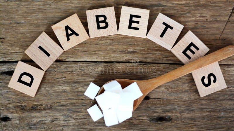 与糖尿病词的高血糖水平概念和在木匙子的白糖立方体在黑暗的背景 免版税库存图片