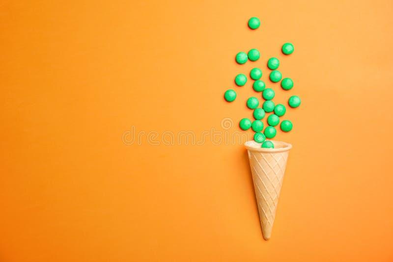 与糖果和冰淇凌的平的位置构成在颜色背景 免版税图库摄影