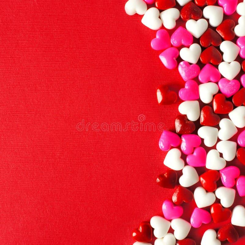 与糖果心脏边界的红色情人节背景 库存图片