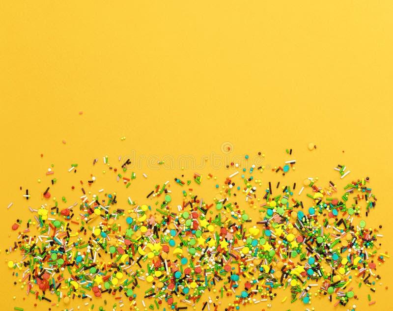 与糖果粉末的复活节装饰五颜六色在黄色背景 免版税库存照片