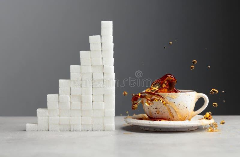 与糖立方体的茶飞溅 免版税库存图片