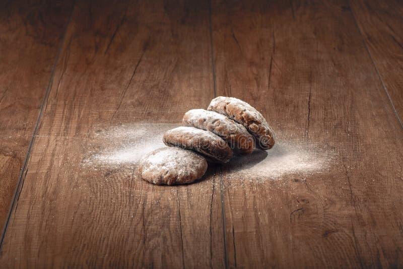 与糖粉末的曲奇饼在一张木桌上 免版税库存照片