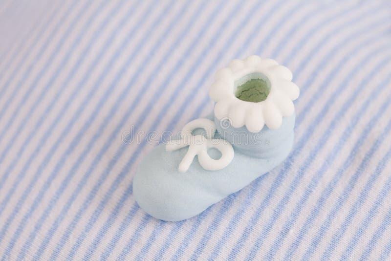 与糖鞋子的镶边婴孩服装 图库摄影