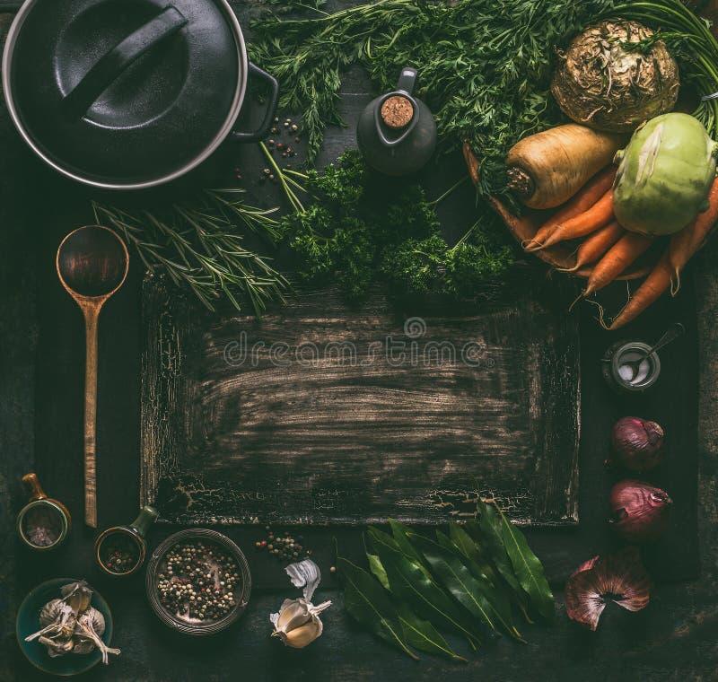 与素食成份的黑暗的土气食物背景框架:根菜类,香料,生铁烹调罐,木匙子 免版税库存照片
