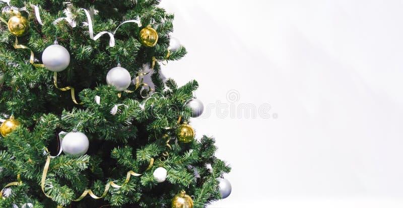 与紧密礼物的装饰的圣诞树在白色背景 用黄色和白色球和闪亮金属片装饰的圣诞树 库存图片