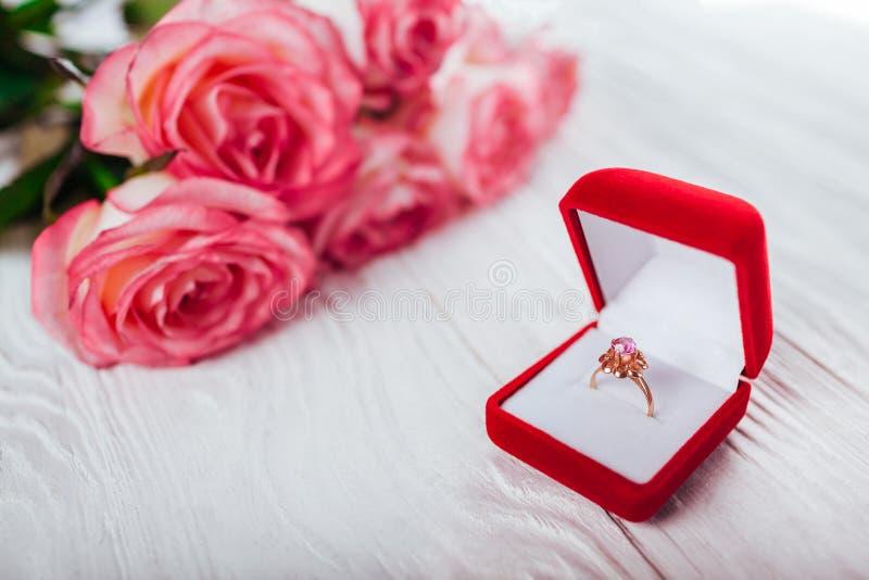 与紫晶的金黄圆环在玫瑰红色礼物盒和花束  日当前华伦泰 库存照片