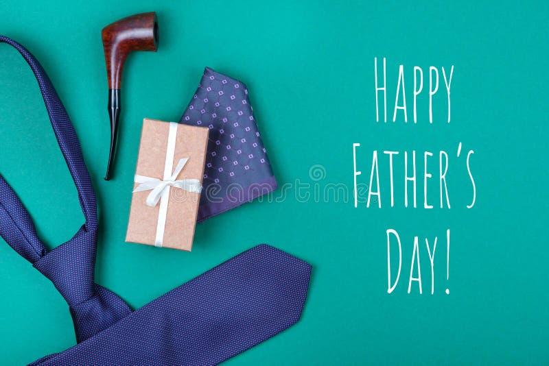 与紫罗兰色脖子领带、礼物盒、口袋正方形和抽烟的烟斗的贺卡与题字愉快的父亲节 库存照片
