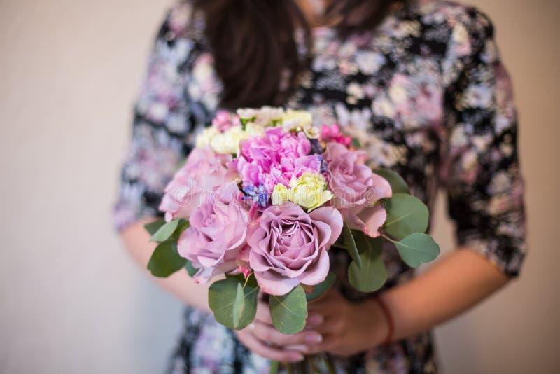 与紫色玫瑰、waxflowers、牡丹、bouvardia、康乃馨和玉树的美丽的混杂的花花束 库存图片