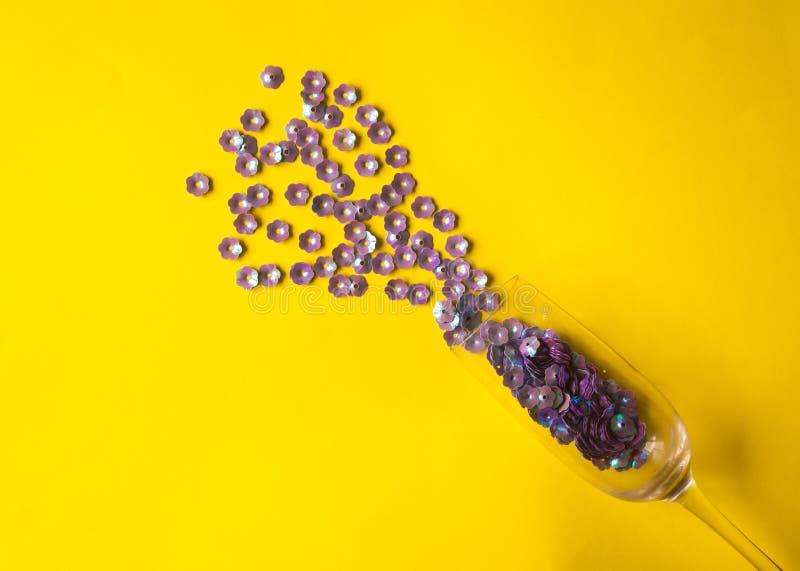 与紫色花卉五彩纸屑的香宾玻璃在黄色背景 免版税库存图片