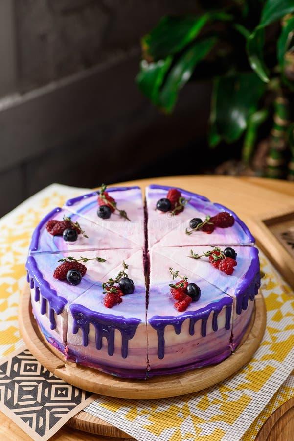 与紫色,白色和桃红色层数的美丽的层状莓果蛋糕,装饰用莓和蓝莓在上面 免版税库存图片