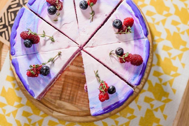 与紫色,白色和桃红色层数的美丽的层状莓果蛋糕,装饰用莓和蓝莓在上面 库存照片